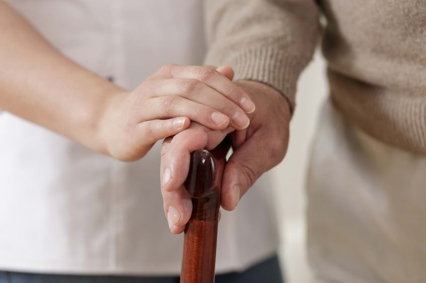 An older person holds a walking stick with a younger person carefully placing their hand on theirs